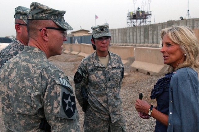 During a 4th of July visit to troops in Iraq, Dr. Jill Biden, the wife of Vice President Joe Biden, speaks with Col. John Norris, commander of 4th Stryker Brigade Combat Team, 2nd Infantry Division, and Capt. Gabriela Niess, the brigade non-lethal planner, in front of the brigade headquarters building.