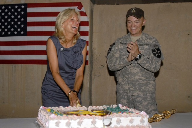 Dr. Jill Biden, wife of Vice President Joe Biden, cuts a 4th of July cake as Col. John Norris, the 4th Stryker Brigade Combat Team, 2nd Infantry Division commander, looks on. Biden stopped by the brigade headquarters for a holiday barbecue during a 4th of July visit to troops in Iraq.