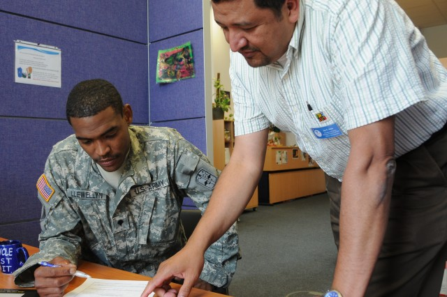 U.S. Army Garrison Grafenwoehr's Exceptional Family Member Program Manager Jay Velis assists Spc. Lawrence Llewellyn, Headquarters Company, 2nd Battalion, 28th Infantry Regiment, review his Exceptional Family Member enrollment status. Soldiers changing stations must ensure their EFMP status is current before they can PCS.