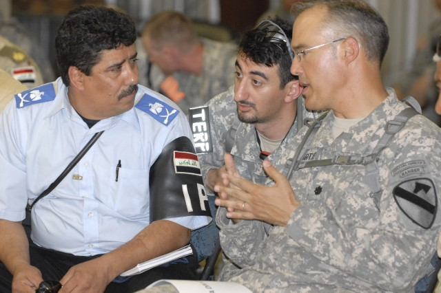 FORT POLK, La. - Lt. Col. Samuel Curtis (right), the Stability Transition Team commander for the 4thBrigade Combat Team, 1st Cavalry Division, speaks with Iraqi role player,  Maj. Gen. Ibrahim Jawad Lutfi Ghazzawi, the Director of the Police Directorate, during a combined arms rehearsal, June 19, at the Joint Readiness Training Center.