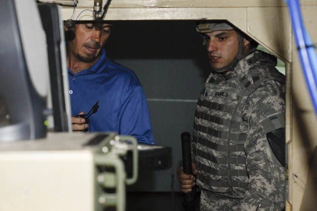 FORT HOOD, Texas-Scott Gurnett (left), a lead Warrior Skills Trainer at Fort Hood's Battle Command Training Center, instructs Sgt. Zachary James, a mechanic with F Forward Support Company, 215th Brigade Support Battalion, 3rd Brigade Combat Team, 1st Cavalry Division on the use of a Blue Force Tracker in a vehicle simulator.