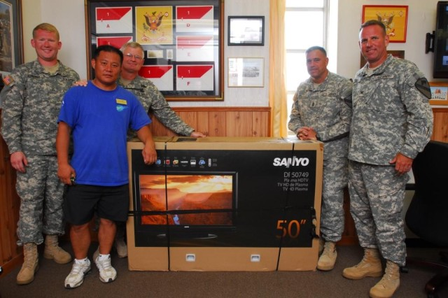 "FORT HOOD, Texas- Col. John Peeler (far right), commander, 2nd Brigade Combat Team, 1st Cavalry Division, and Command Sgt. Maj. Emmett Maunakea (second right), received a 50-inch television on behalf of ""Black Jack"" Soldiers from the Fort Hood Better Opportunities for Single Soldiers program, July 6, for the effort the brigade put into planning and hosting the Fort Hood Single Soldiers' Festival."