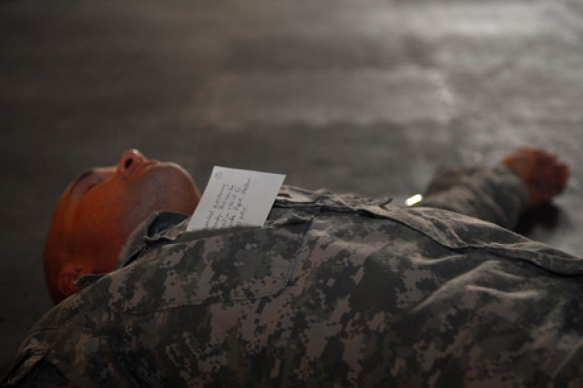 Spc. Matt Edgeworth, of Cleveland, Tenn., a light-wheel vehicle mechanic with 252nd Military Police Co., lays waiting as a mock-casualty for the first medical responders at the gym during the start of a mass casualty exercise conducted on Contingency Operating Base Delta, June 25, 2010. Cards on the players listed their injuries.