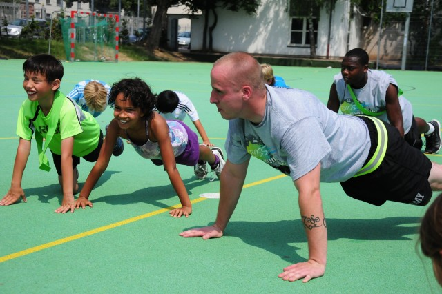 Spc. William Perkins, Heidelberg Better Opportunities for Single Soldiers program president leads fourth graders from the Englisches Institut Grundschule in a push-up session following a friendly game of kickball during the students' sports lesson.