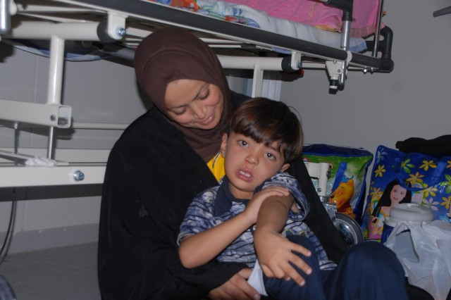A Mother and son relax in the recovery room after a cleft palate and lip repair at the Mittica Medical Training Center in Nasiriyah, Iraq June 23. (Photo by Spc. Chastity R. Boykin, 3rd BCT, 4th Inf. Div.)