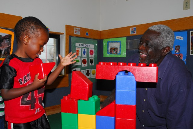 Christopher Royal, 2, and Thomas Manigo, director of the Scales Child Development Center, build a block castle. Manigo, who once pursued a career in acting, will retire in August, ending his 26 years as the center's director.