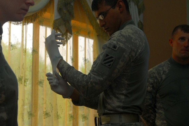 Spc. Joel Obregon, a medic with 1st Battalion, 10th Field Artillery Regiment and native of Austin, Texas, dons a latex glove in preparation to see local Iraqis from the Anwar district in the city of al-Kut.