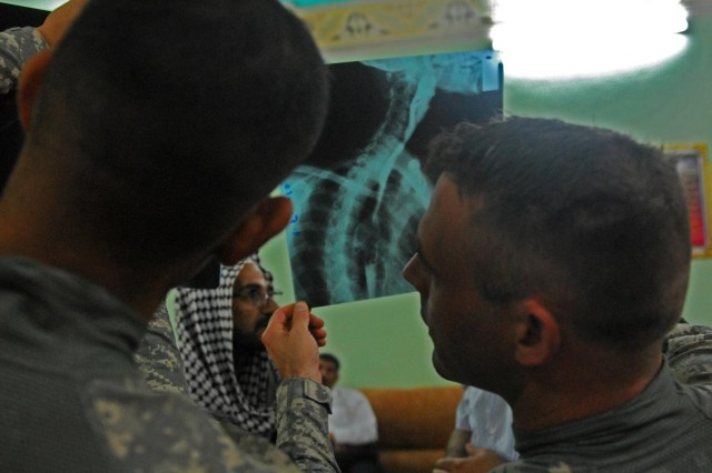 Spc. Miguel Ocegueda, a medic with 1st Battalion, 10th Field Artillery Regiment and native of Austin Texas, and Capt. Matthew Holt, 1st Bn., 10th FA Regt. physician's assistant from Atlanta, assess X-rays brought in by a local Iraqi man from the Anwar district in the city of al-Kut.
