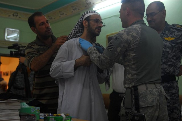 Sgt. 1st Class Gregory Lurker, the medical platoon sergeant with 1st Battalion, 10th Field Artillery Regiment and a native of Birmingham, Ala., assesses a local Iraqi man from the Anwar district in the city of al-Kut.