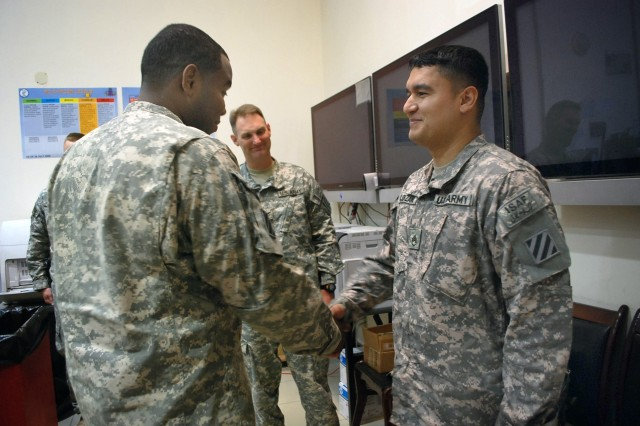 Sgt. Roberto Solorzano (right), Headquarters and Headquarters Company, 3rd Combat Aviation Brigade, Task Force Falcon, from Houston, is promoted to the rank of staff sergeant, by Sgt. 1st Class Jesse Fennell, HHC, 3rd CAB, TF Falcon, from Salisbury, Md., at Bagram Airfield, Afghanistan, July 5.