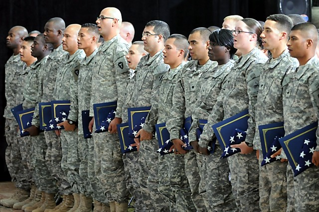A group of Soldiers, Sailors and Airmen stationed throughout Iraq say the Pledge of Allegiance for the first time as U.S. citizens at Camp Victory, July 4. During the naturalization ceremony, the 17th conducted on Camp Victory since U.S. forces arrived to Iraq in 2003, 156 servicemembers from 56 different countries officially became U.S. citizens.