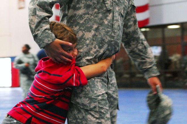 A child grips his father as he readies to deploy after a deployment ceremony held for the 581st Area Support Medical Company, 61st Multi-functional Medical Battalion, 1st Medical Brigade, 13th Sustainment Command (Expeditionary) and 59th Transportation Detachment held at Abram's Field House on Fort Hood, Texas July 3. The units are headed to Afghanistan for a 12 month rout of duty. (U.S. Army photo by Spc. Alisha Hauk)