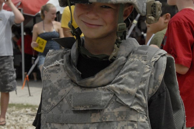 FORT HOOD, Texas-Gage Beals (7),  from Killeen, Texas, has a few more years to wait before he can enlist, but he tries on the Army Advanced Combat Helmet and Improved Outer Tactical Vest for size during Fort Hood's Freedom Festival at Fort Hood Stadium, July 4.