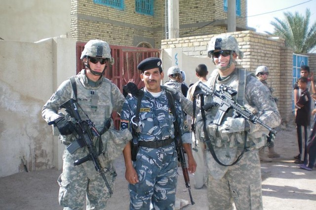 Capt. Zachary Quintana of Phoenix, Ariz., and Capt. Brian Ivany of Washington, D.C., pose for a picture with an Iraqi policeman from Al Shatrah Police Department during Human Terrain Analysis Team operations in Al Gharraf.