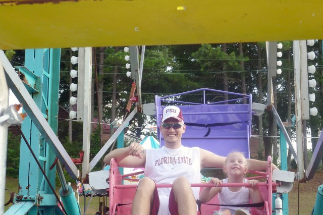 Jerry Anderson, husband of Sgt. Erika Anderson, video teleconference technician, Third Army/U.S. Army Central, and their 6-year-old daughter, Ashley, take a ride on a Ferris wheel during Fort McPherson's Independence Day celebration July 1. The event featured rides, food and fireworks for servicemembers, Civilian employees, Family members, and retirees.