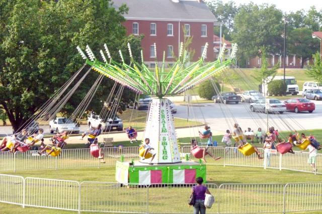 Fort McPherson children swing through the air as they ride a Tilt-a-Whirl set up as part of the Fort McPherson Independence Day celebration.