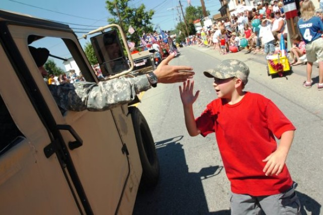 """CANONSBURG, Pa. -- A child greets Army Spc. Salvatore Norge, of West Pittsburg, Pa., and Soldier with the 301st Regional Support Group, Butler, Pa., with a high-five during the Fourth of July parade here on Saturday, July 3.  The supporter is one of nearly 50,000 parade-goers who attended the event.  In its 48th year, the parade continues to be one of the state's largest parades. This year's parade theme was """"Honoring those who have served."""""""