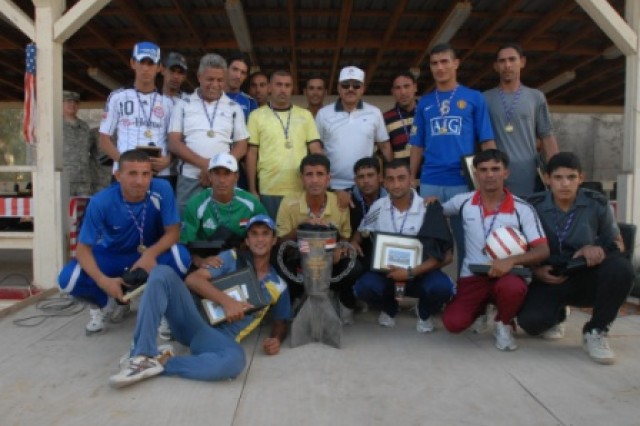 Winners of the Brothers-In-Arms Soccer Tournament pose with the trophy following the awards presentation July 4 at Contingency Operating Site Echo, Iraq.  Players were presented a medal, framed team photograph, and a certificate of appreciation for their participation in the event.