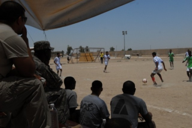 Soldiers from 1st Battalion, 15th Infantry Regiment, 3rd Heavy Brigade Combat Team, 3rd Infantry Division watch as the Iraqi Army and Iraqi Police soccer teams play during the Brothers-In-Arms Soccer Tournament July 4 at Contingency Operating Site Echo, Iraq. The tournament was followed by an awards ceremony, a cookout, and live music.