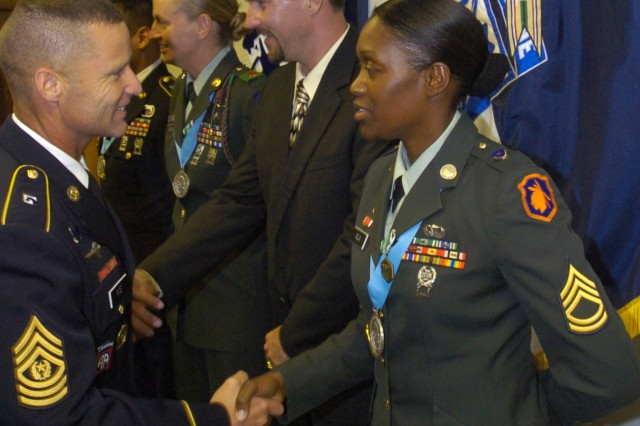 Sergeant 1st Class Renee Nolin, 108th Training Command, is congratulated June 25, by XVIII Airborne Corps Command Sgt. Maj. Earl. L. Rice after her induction into the post chapter of the Sgt. Audie Murphy Club held at Memorial Hall.