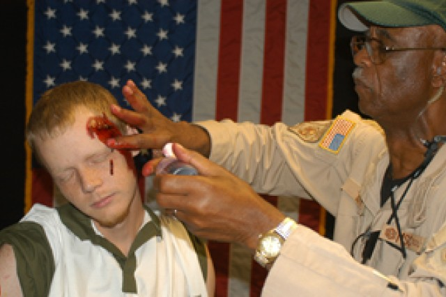 C.W. Lott applies fake blood to Joshua Arnold, a roleplayer at the Joint Readiness Training Center June 28, in preparation for a simulated mass-casualty event.