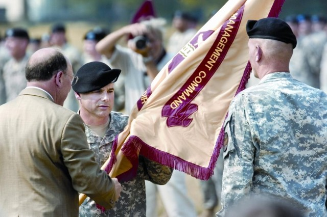 Russell B. Hall, left, hands the unit colors to incoming commander Col. John J. Strycula, center, taking over from Col. Jerry L. Blixt at the Change of Command Ceremony in front of Abbot Hall at Fort Belvoir on Wednesday.