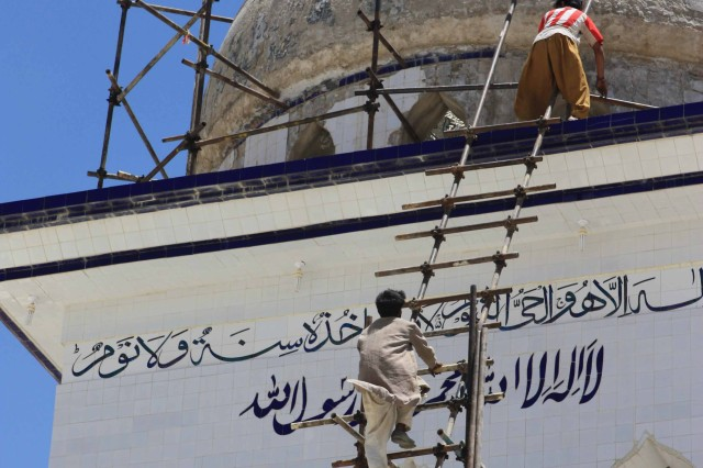Afghan workers in Khakrez District, north of Kandahar city, work on the minaret of the Ziarat-e Shah Maqsud Shrine, the third most holy site in Afghanistan June 14, 2010.  U.S. Special Operations Forces are assisting in the refurbishment of the shrine.