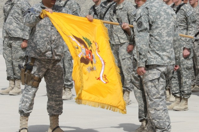 Lt. Col. Andrew Green, Commander of 4th Squadron, 2nd Stryker Cavalry Regiment unfurls the squadron colors during a transfer of authority ceremony held recently at Forward Operating Base Spin Boldak in southern Afghanistan