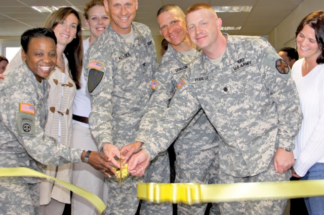 Col. Patrick Matlock, 170th Infantry Brigade Combat Team commander, Lt. Col. Paul Pfahler, U.S. Army Garrison Baumholder commander, other leaders and spouses cut the yellow ribbon spanning the doorway to the new Yellow Ribbon Room.