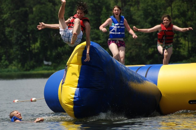 Wyatt Watkins, of Montgomery, Ala., anticipates the cold chill of the lake water as he is catapulted off the aqua-tramp and into the air. Watkins and many other military youth enjoyed the thrill of the aqua-tramp at the Alabama Guard's youth camp held at the 4-H Center in Columbiana, Ala.
