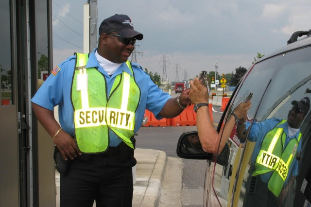 Marvin Williams, a security guard with Costal International Security, checks an identification card at the entrance to the U.S. Army's Detroit Arsenal in Warren, Mich.