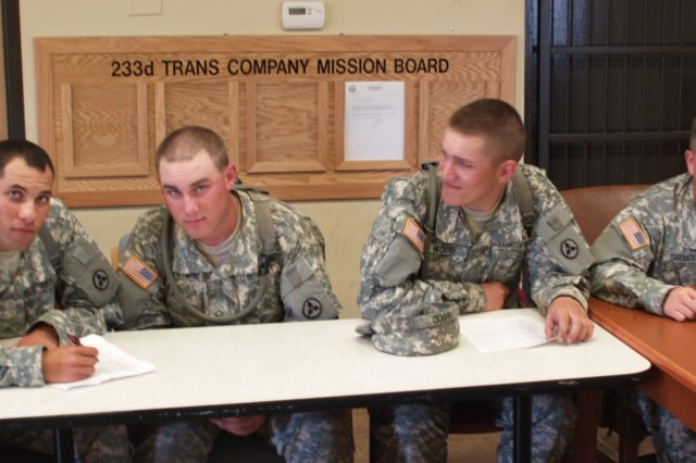 233rd Transportation Company Soldiers, Pvt. Kenne Goode, Pvt. 1st Class Jonathan Entwhistle, Pvt. Matthew Woode, and Spec. Joshua Bryant, study for the HET driver training final written exam in the 233rd motor pool conference room June 22. All four Soldiers went on to graduate and become fully licensed HET drivers. (U.S. Army Photo by 2nd Lt. Sean Chang)