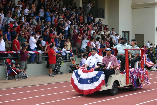 """HONOLULU — Summer school students hold signs that read, """"We Salute You. Mahalo!"""" as three Soldiers from Schofield Barrack's Warrior Transition Battalion lead the 22nd Annual Iolani School Independence Day Parade, at Kozuki Stadium, here, July 2. The Soldiers were honored and thanked for their service during the patriotic program."""