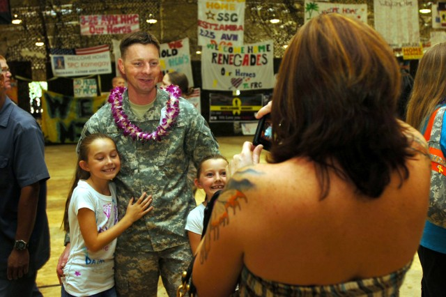 A warrant officer with the 25th Combat Aviation Brigade poses for a family photo for his wife during the Welcome Home Ceremony held at Wheeler Army Airfield, Hawaii, July 12, in honor of the Soldiers of the 25th Combat Aviation Brigade's successful 12-month rotation to northern Iraq. During the emotional ceremony, the combat veterans of the 25th CAB were reunited with their families and friends for the first time since the brigade departed last year. (U.S. Army photo by Spc. Jesus J. Aranda, 25th Infantry Division Public Affairs Office)