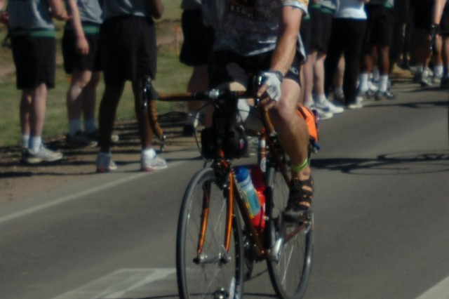 Chad Jukes, a cyclist participating in the Sea to Shining Sea program, waves his prosthetic leg in victory as he arrives at Fort Carson's Iron Horse Park June 16. Jukes lost his leg after his truck was struck by an anti-tank mine while serving in Iraq. Jukes said the 4,000-mile journey from San Francisco to Virginia Beach, Va., is the first long-distance cycling event he has ever undertaken.