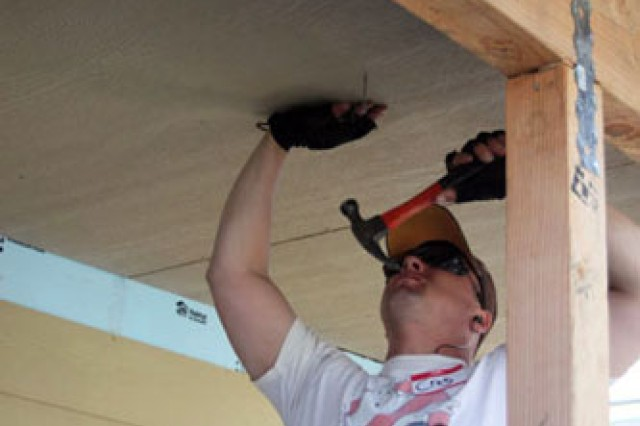Spc. Michael Ballard and Sgt. 1st Class Kevin Broadway measure and cut a piece of siding to fit around a window frame.