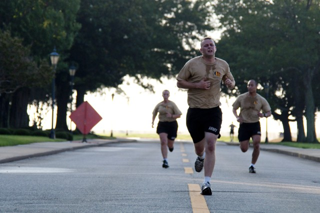 Staff Sgt. Dustin Hinze, a competitor, is close to the finish line of the two mile run as Staff Sgt. Russell Kojo, a competitor who has deployed six times in support of both Operations Iraqi and Enduring Freedom, motivates fellow competitor, Spec. Sherri Gallagher on her last leg during the 2010 U.S. Army Training and Doctrine Command Noncommissioned Officer and Soldier of the Year Competition on Fort Monroe, Va., July 13. The competitors completed the Army Physical Fitness Test early on the second day of the competition. (U.S. Army photo by Sgt. Angelica Golindano)(RELEASED) 100713-A-0928G-028