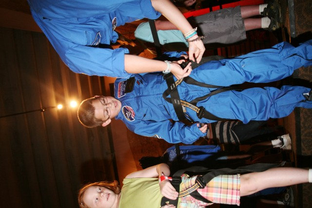 A Space Camp Team Leader helps a scholarship recipient put on a harness before he attempts the rock climbing wall at the U.S. Space and Rocket Center July 7.