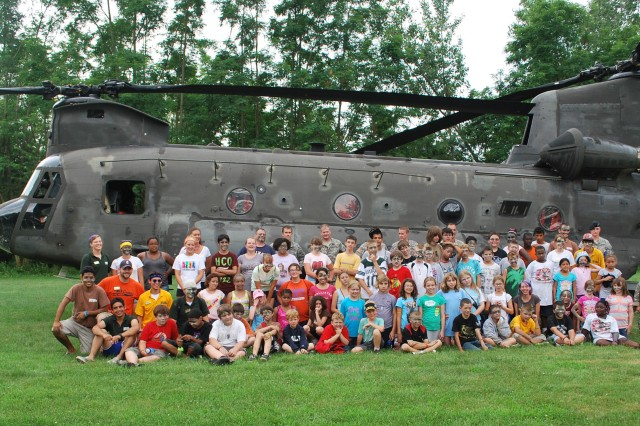 Camp participants pose with Iowa National Guard Soldiers and a CH-47 Chinook, July 7 at Camp Abe Lincoln, Blue Grass, Iowa.