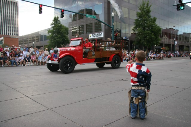 """COLORADO SPRINGS, Colo.-A """"Cowboy"""" waves to the US Air Force Academy's antique fire truck at the Pike Peak or Bust Rodeo Parade July 13. The rodeo raises funds for local military charities."""