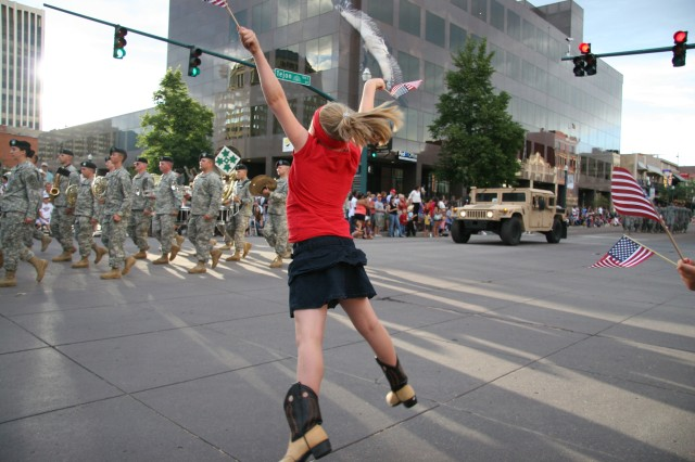 COLORADO SPRINGS, Colo.-A cheer goes up for the 4th Infantry Division Band and Soldiers at the Pike Peak or Bust Rodeo Parade July 13. The rodeo raises funds for local military charities.