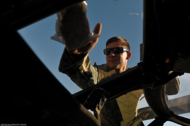 Cleaning the windshield of a UH-60 Black Hawk, Spc. Tony Moreno, a crew chief with Co A., 2-25th Combat Aviation Brigade, attached to 2nd Heavy Brigade Combat Team, 3rd Infantry Division, prepares the cockpit for the pilots, who will be flying the day's mission from Contingency Operation Site Diamondback, Mosul, Iraq, July 2.
