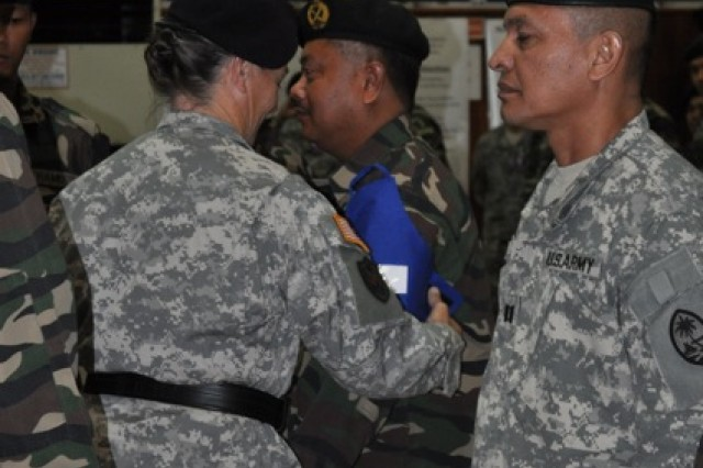 Brig. Gen. Michele G. Compton, the commanding general of the Army Reserve's 9th Mission Support Command places an armband around one of the Malaysian leaders during the opening ceremony of Keris Strike 2010, July 12.  Keris Strike 2010, a bilateral effort co-sponsored by U.S. Army, Pacific and the Malaysian armed forces, is designed to strengthen U.S. Malaysian relations and further build on the peace support operational capacity of its participants.
