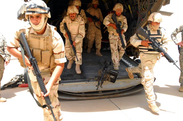Commandos of the 10th Iraqi Army Division commandos race off the ramp of a CH-47 Chinook helicopter during the dry-run portion of their air assault training at Forward Operating Base Garryowen, Iraq, June 28.