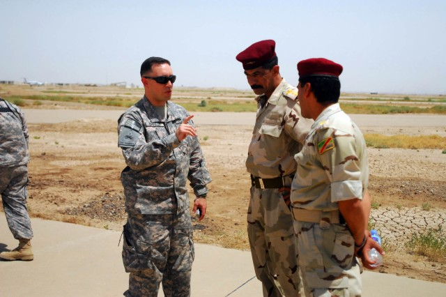 Maj. Mike Bagully, a native of Maybee, Mich., and training advisor for the 10th Division Military Transition Team under 1st Infantry Division, speaks with one of the Iraqi general officers and his staff prior to the 10th Iraqi Army Division commandos starting a training mission at Forward Operating Base Garryowen, Iraq, June 28.