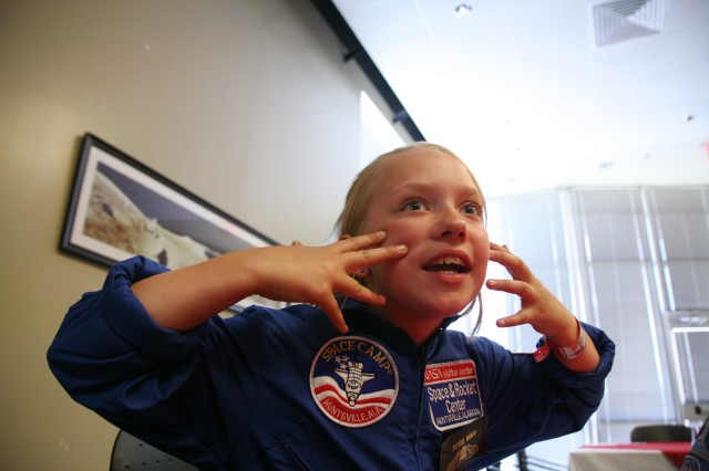 Aurora Truelove, 10, explains how the G-force of a simulator pulls the face back at a luncheon July 7 to honor Space Camp scholarship recipients and the Air, Space, and Missile Defense Association, the organization that awarded the scholarships. Truelove is a fifth grader in Delta Junction, Alaska.