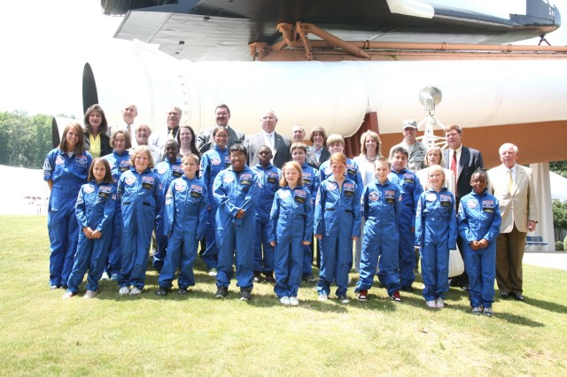 All sixteen scholarship recipients, the group's team leader, and Air, Space, and Missile Defense Association representatives pose for a photo in front of the space shuttle on display at the U.S. Space and Rocket Center July 7.