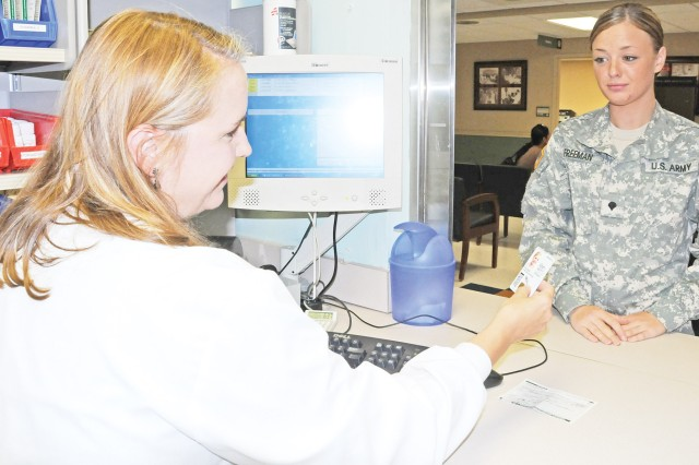 Lyster Army Health Clinic Staff Pharmacist Kaye White fills a prescription for Spc. Chelsea Freeman July 8. Pharmacy staff has recently updated and expanded services to better serve customers' needs.