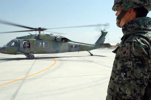 A Soldier in Task Force Taegeuk, the Republic of Korea Army aviation unit working with the 3rd Combat Aviation Brigade, TF Falcon, watches as a ROK Black Hawk prepares to fly its mission at Bagram Airfield, Afghanistan, July 8.