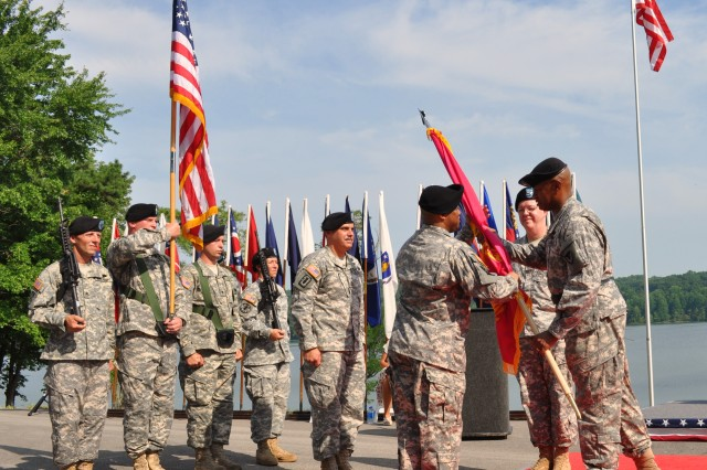 Col. Linwood Clark (3rd from right) takes the Crane Army flag from Joint Munitions Command Commanding General Brig. Gen. Larry Wyche (far right), signifying his acceptance of command of Crane Army Ammunition Activity.  Looking on are former CAAA Commander Col. Charles Kibben (2nd from right) and JMC Command Sergeant Major David Puig (4th from right).